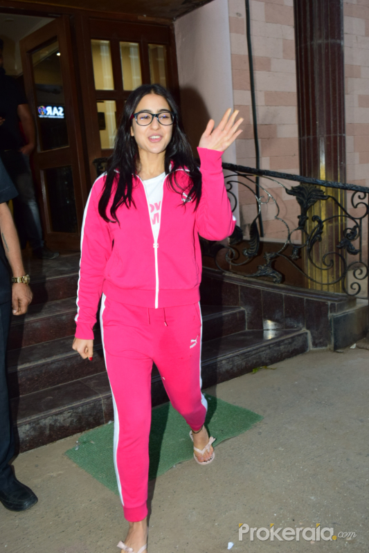 Actress Sara Ali Khan waving and smiling at fans