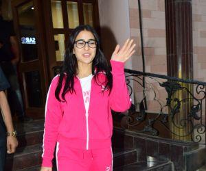 Actress Sara Ali Khan waving and smiling at fans
