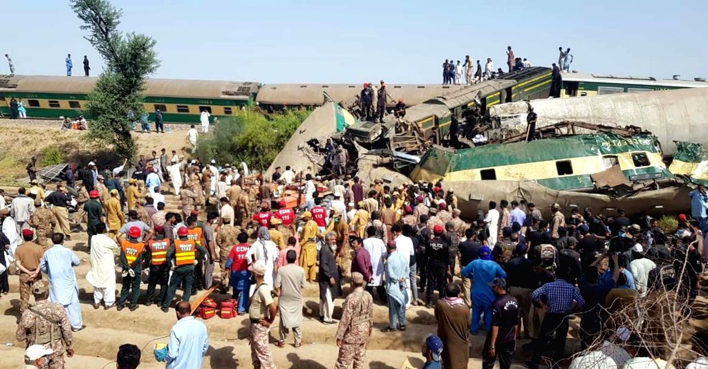 07 June 2021, Pakistan, Ghotki: Army officials and rescue workers gather at the site following a collision between two trains between the Raiti and Obaro railway stations. At least 41 people are dead ...