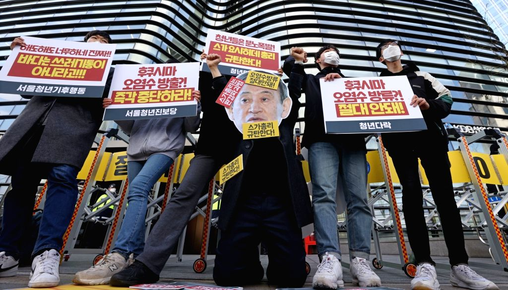 13 April 2021, South Korea, Seoul: South Korean civic activists hold placards as they take part in a protest in front of the Japanese Embassy in Seoul against the Japanese government's decision to ...