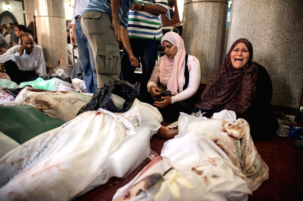 An Egyptian woman cries beside a dead body at a mosque where lines of bodies wrapped in shrouds were laid out in Cairo, Egypt, Aug. 15, 2013. At least 525