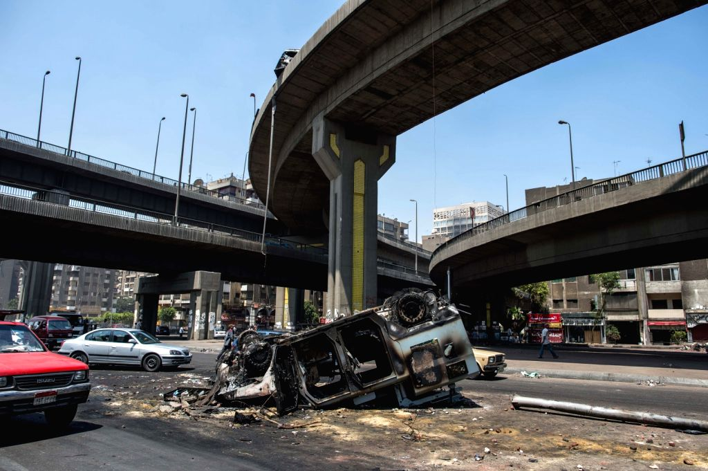 Photo taken on Aug. 15, 2013 shows a burned police vehicle in Cairo, Egypt. Egyptian authorities raised the death toll from clashes the previous day ...