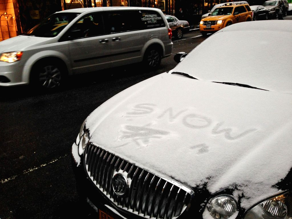A vehicle goes past another one covered in snow during a snowfall in New York, the United States, Jan. 6, 2015.