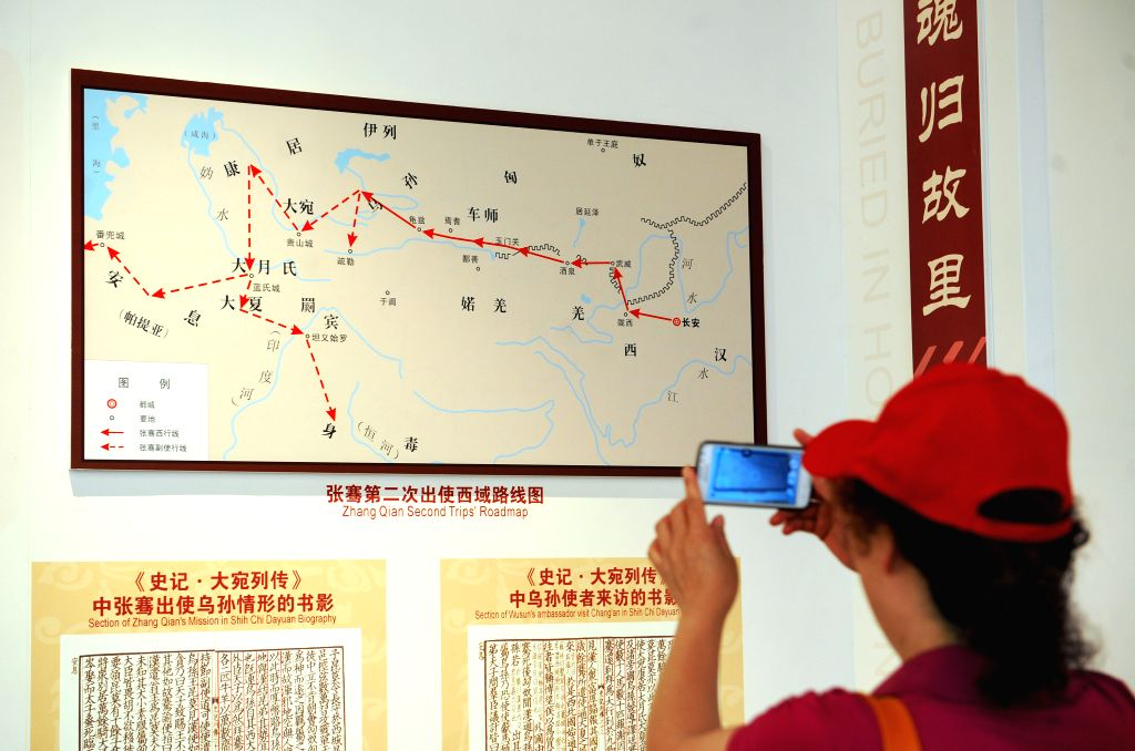 A tourist takes photos of a roadmap showing Zhang Qian's second trip to the West at the Tomb of Zhang Qian in Chenggu County of Hanzhong, northwest ...