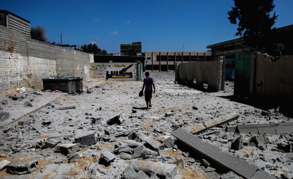 A Palestinian inspects the damage at Ali ibn Abi Taleb government school that was targeted overnight by Israeli airstrikes in Gaza City, on August 26, ...