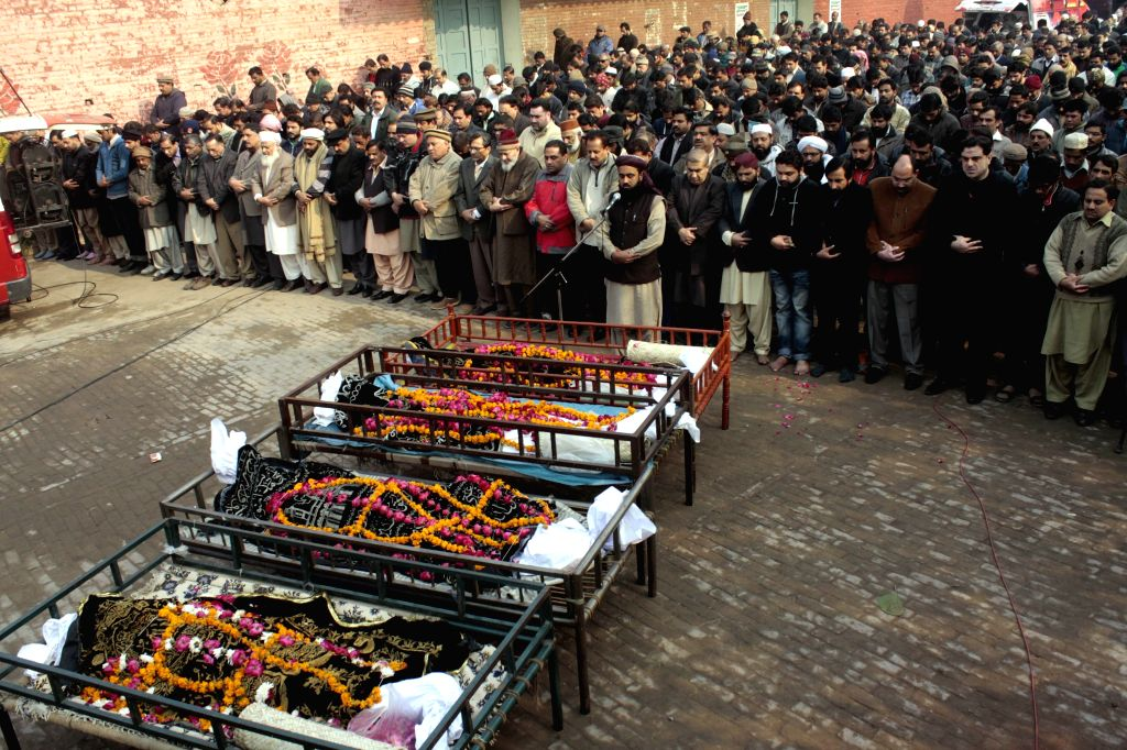 Mourners attend a funeral ceremony of victims of a fire in a four-story shopping plaza in east Pakistan's Lahore, on Dec. 30, 2014. At least 13 people ...