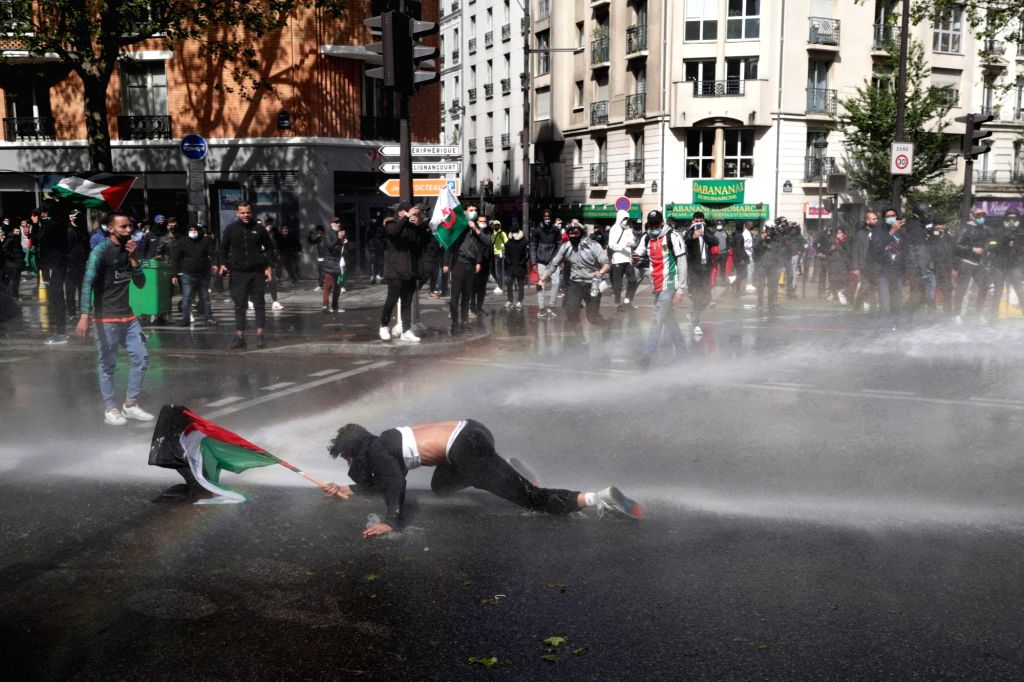 15 May 2021, France, Paris: A protester tries to get up while being sprayed by a water canon during an illegal demonstration in solidarity with Palestinians amid the escalating flare-up of ...