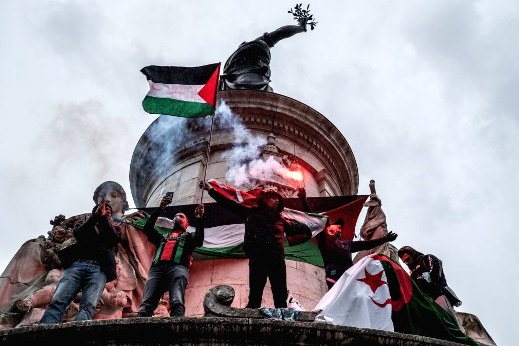 15 May 2021, France, Paris: Demonstrators wave Palestinian flags and light flares during an illegal demonstration in solidarity with Palestinians amid the escalating flare-up of Israeli-Palestinian ...