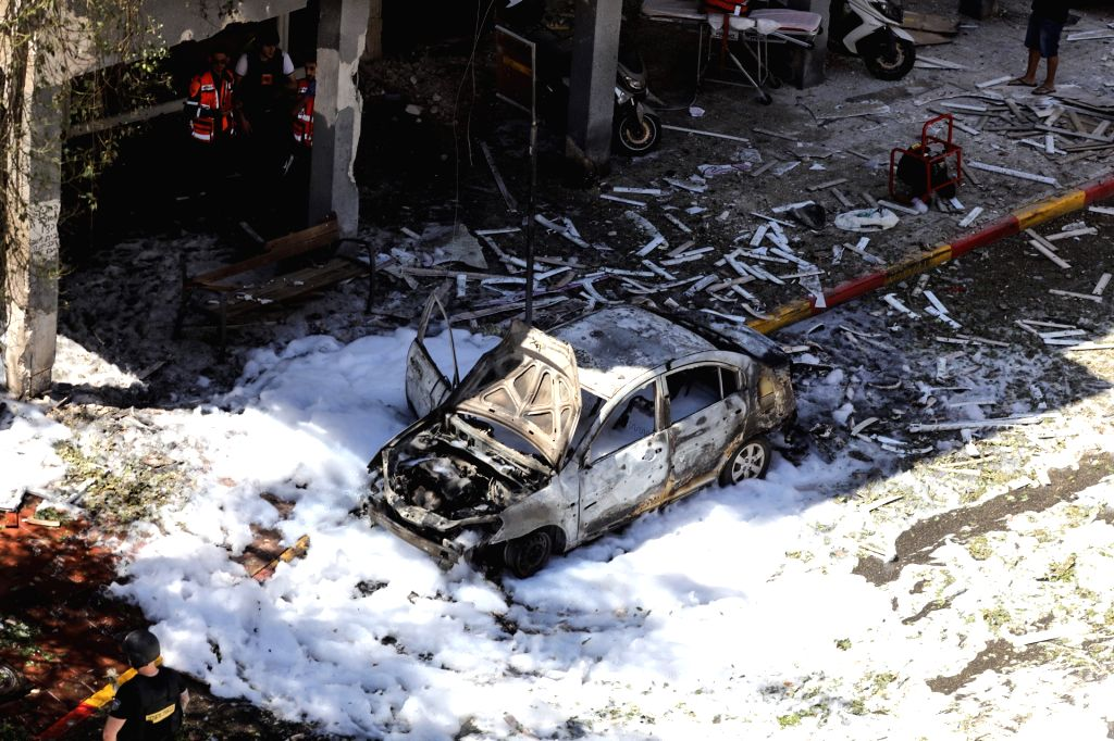 15 May 2021, Israel, Ramat Gan: A burnt car is seen in front of a damaged house that was hit by a rocket fired by the Palestinian Islamist movement Hamas from Gaza towards Israel, amid the escalating ...