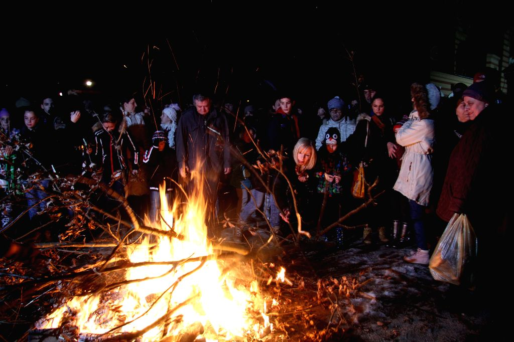 People burn dried oak branches, the Yule log symbol for the Orthodox Christmas Eve in front of Church of St. Troy, in Banja Luka, northern Bosnia and .
