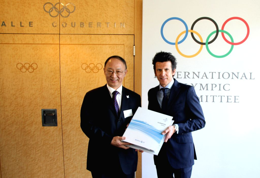 IOC Sports Director Christophe Dubi (R) receives from the hands of Minister of the General Administration of Sport of China and Chairman of the Chinese ..