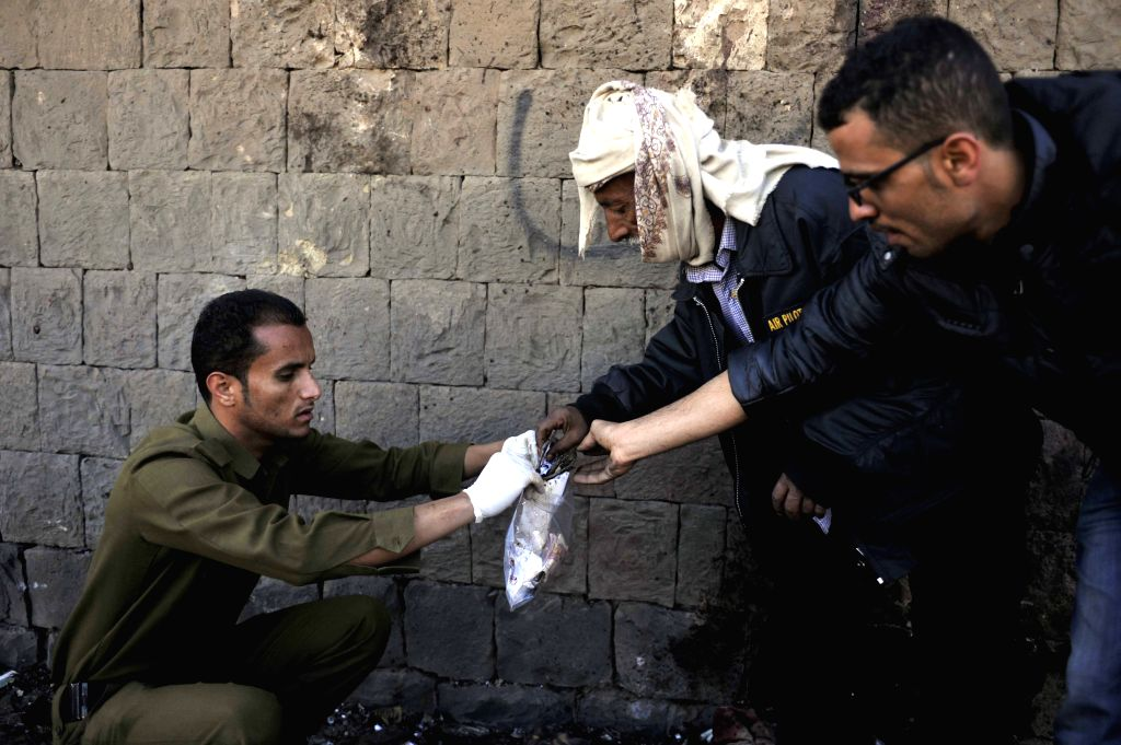 A policeman collects evidence at the blast site in Sanaa, Yemen, on Jan. 7, 2015. At least 50 people were killed and 20 others wounded early Wednesday when .