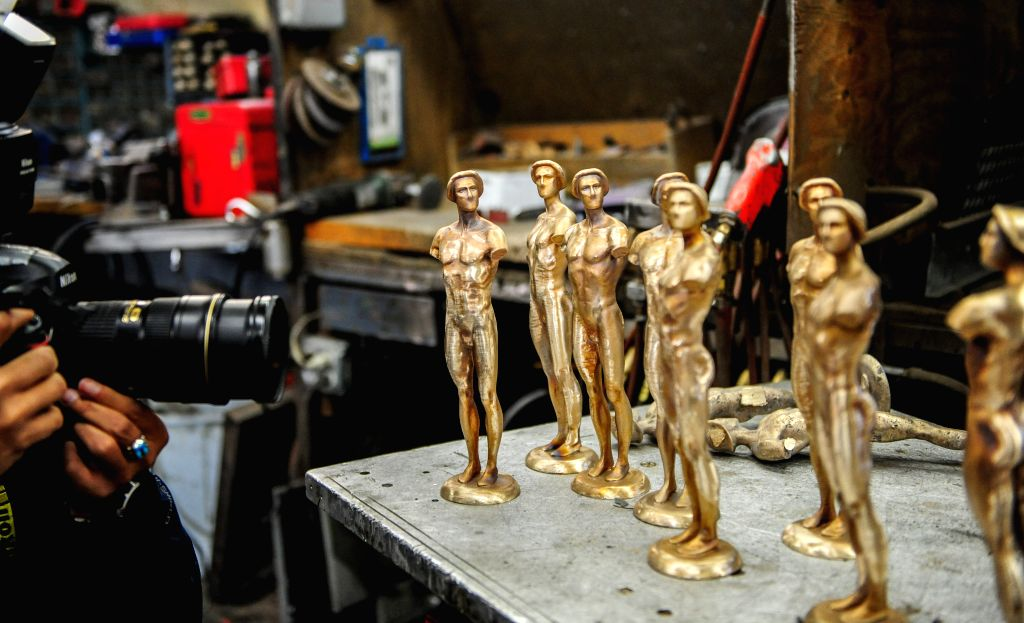 Workers prepare to take molds out of a furnace during a media event to display the production of the bronze statuette awards for the 21st annual Screen . - Guild