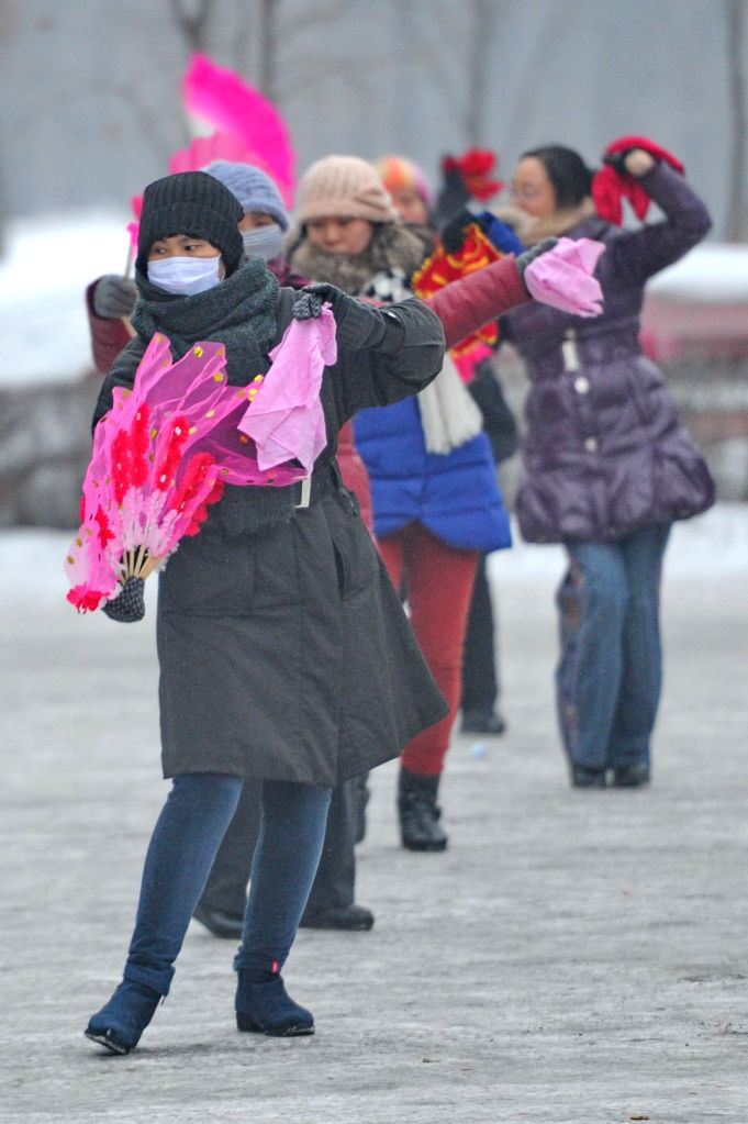Local residents wearing masks do morning exercises at the smog-shrouded Nanhu Park in Changchun, capital of northeast China's Jilin Province, Jan. 14,