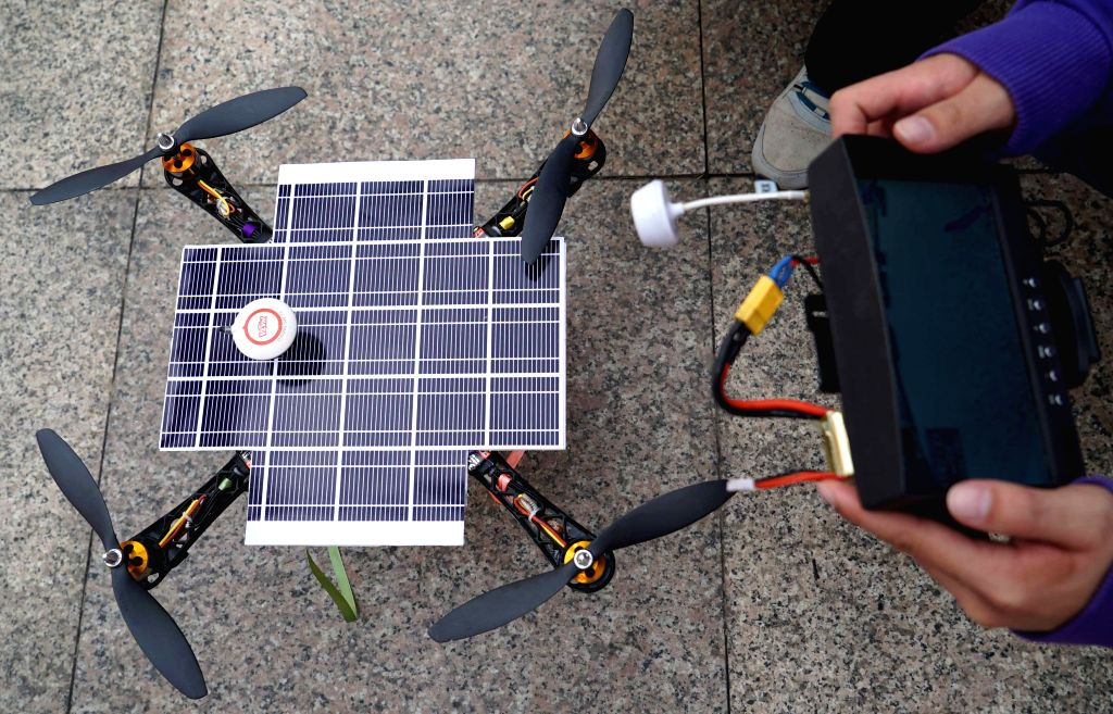 A student of Nanchang Hangkong University (NCHU) adjusts a solar-powered drone in Nanchang, east China's Jiangxi Province, Jan. 14, 2015. Designed by .