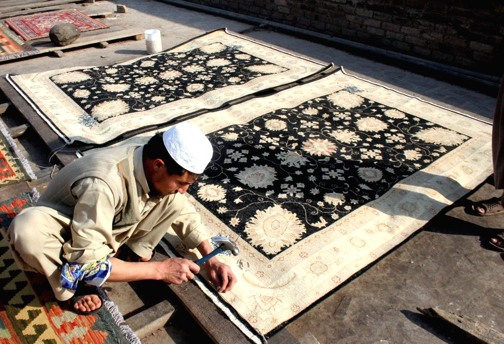 A Pakistani man crafts handmade carpets at a factory on the outskirts of northwest Pakistan's Peshawar, Jan. 15, 2015.