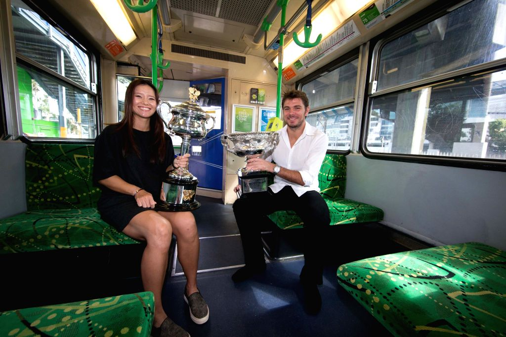 Former Chinese tennis player Li Na (L) and Swiss tennis player Stan Wawrinka arrive at Melbourne Park by a tram to attend the official draw ceremony ..