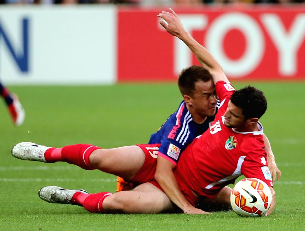 Japan's Shinji Okazaki (L) fights with Jordan's Anas Bani during their third round match of Group D at the 2015 AFC Asian Cup tournament in Melbourne,