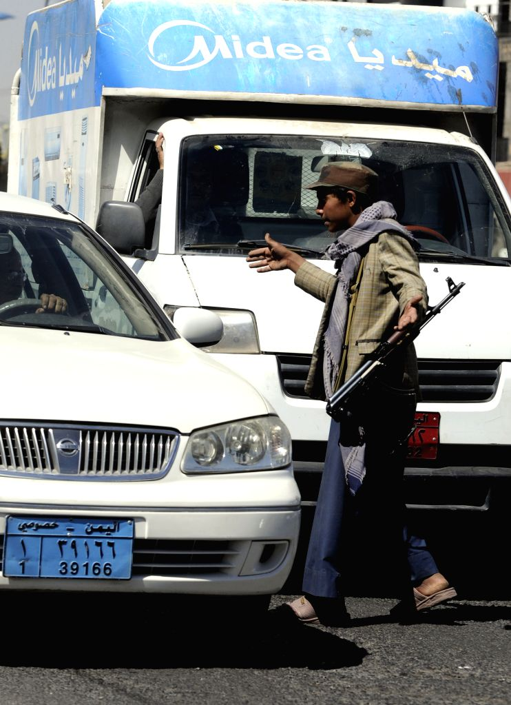 A Houthi fighter checks cars on a road leading to the house of President Abd-Rabbu Mansour Hadi in Sanaa, Yemen, on Jan. 21, 2015. Tensions mounted in ...