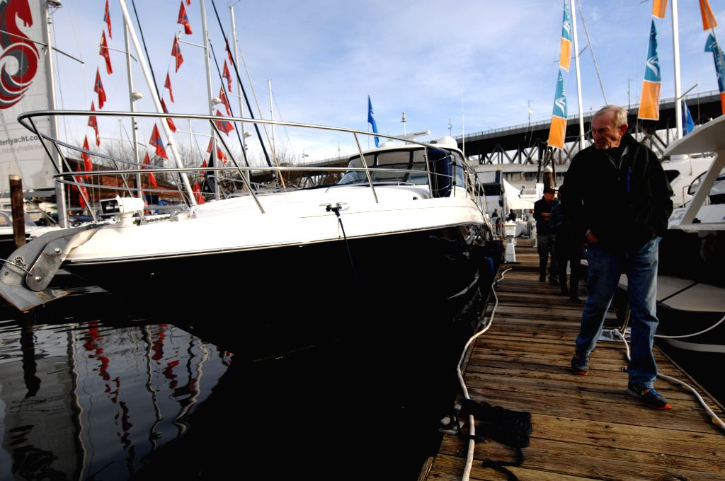 A visitor looks at a boat at the 2015 Vancouver International Boat Show at BC Place in Vancouver, Canada, Jan. 21, 2015. Canada's premier 5-day ...