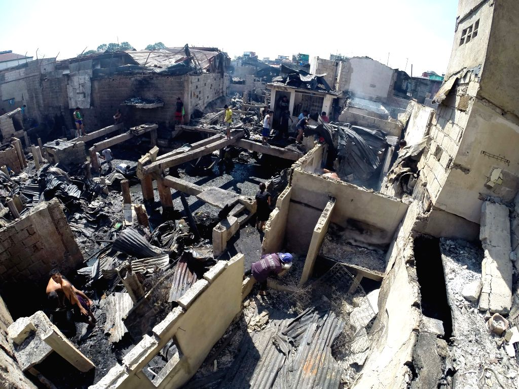Residents scavenge for their belongings from their charred homes after a fire at a slum area in Pasay City, the Philippines, Feb. 16, 2015. At least .