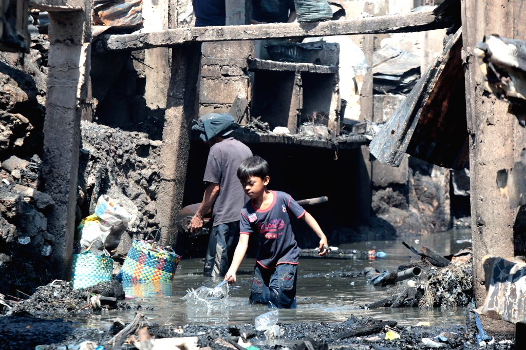Residents scavenge for their belongings from a creek after a fire at a slum area in Pasay City, the Philippines, Feb. 16, 2015. At least four people .