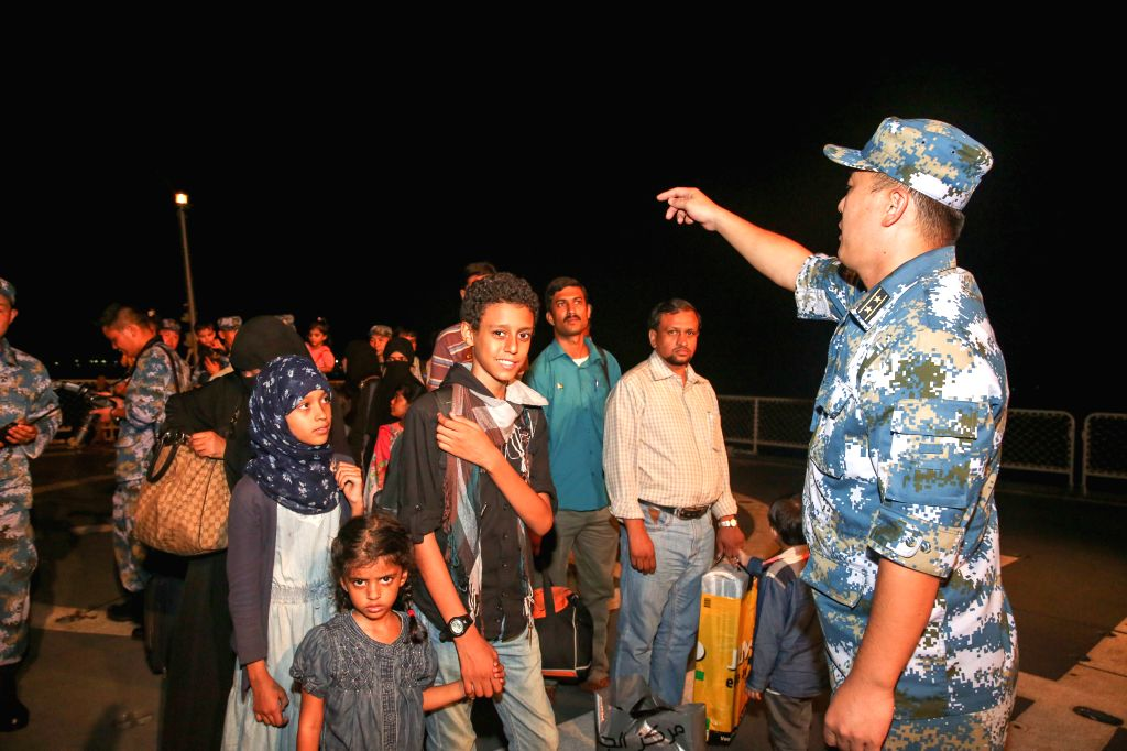People wait to step down the Chinese Linyi missile frigate when they arrive in Djibouti, April 2, 2015. A total of 225 nationals from 10 countries who ...