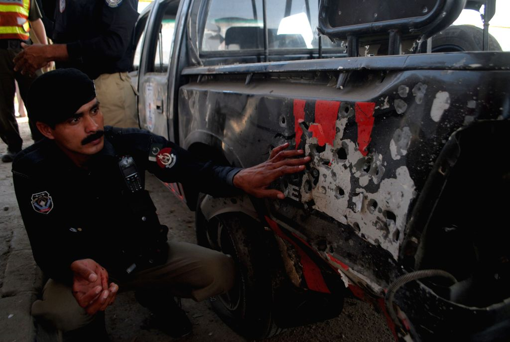 A policeman inspects a damaged vehicle at the blast site in northwest Pakistan's Peshawar on April 24, 2015. At least five policemen were injured when ...