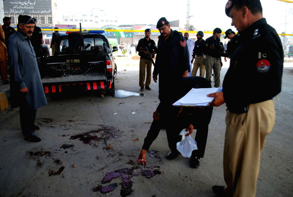 Policemen inspect the blast site in northwest Pakistan's Peshawar on April 24, 2015. At least five policemen were injured when a bomb hit their ...