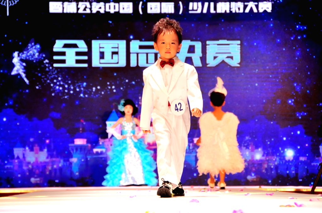 A boy shows a suit during a children's model contest in Beijing, capital of China, Aug. 17, 2015.  More than 170 children took part in the final of a ...
