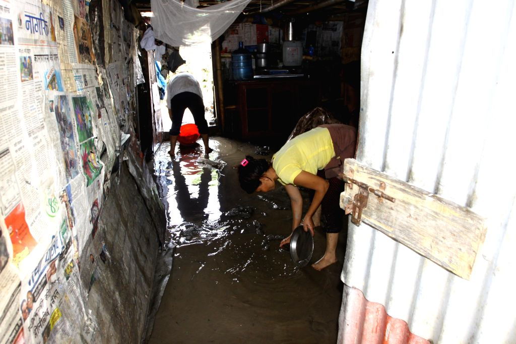 A family clears out water in a shed after floodwater flowing from the swollen Bagmati river to a slum area at Gairigaon in Kathmandu, Nepal, Aug. 17, ...