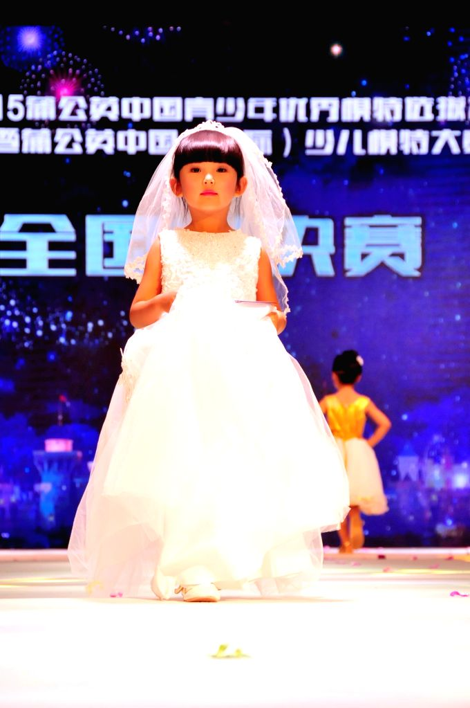A girl shows her dress during a children's model contest in Beijing, capital of China, Aug. 17, 2015. More than 170 children took part in the final of a ...