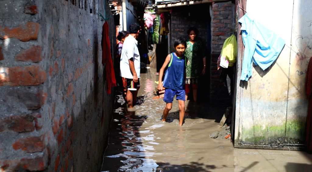 People walk through a flooded area in a slum area at Gairigaon in Kathmandu, Nepal, Aug. 17, 2015. Around 200 families living in the slum area were ...