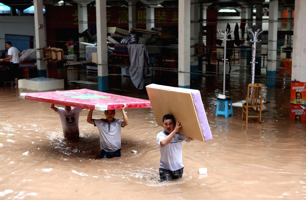 Residents carry property in the flood water in Jinlong Township of Yongchuan District, southwest China's Chongqing Municipality, Aug. 17, 2015. A ...