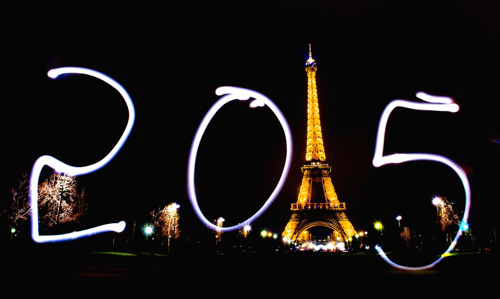 """A tourist writes """"2015"""" with a light pen in front of the Eiffel Tower in Paris, France, Dec. 30, 2014."""