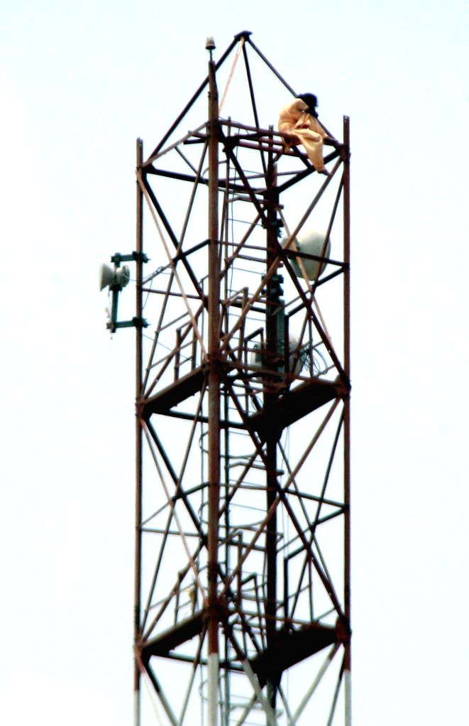 A 28-year-old woman climbs-up a mobile phone tower after being harassed by a man in Gurgaon on Aug 4, 2014.