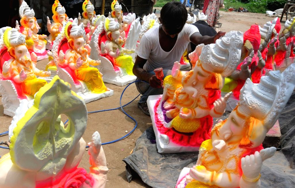 A artist paints idols of lord Ganesh on the outskirts of Amritsar  on Aug 1, 2016.