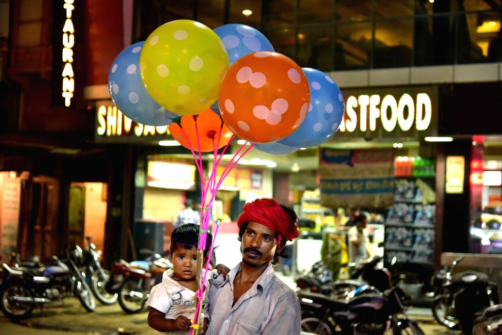 A balloon seller carries his child as he sells balloons during Navratri in Bikaner on Oct 7, 2016.