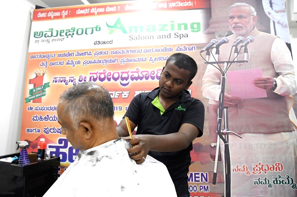 A barber gives a free haircut on the occasion of the swearing in ceremony of Prime Minister Narendra Modi for the second consecutive term, in Bengaluru on May 30, 2019. - Narendra Modi