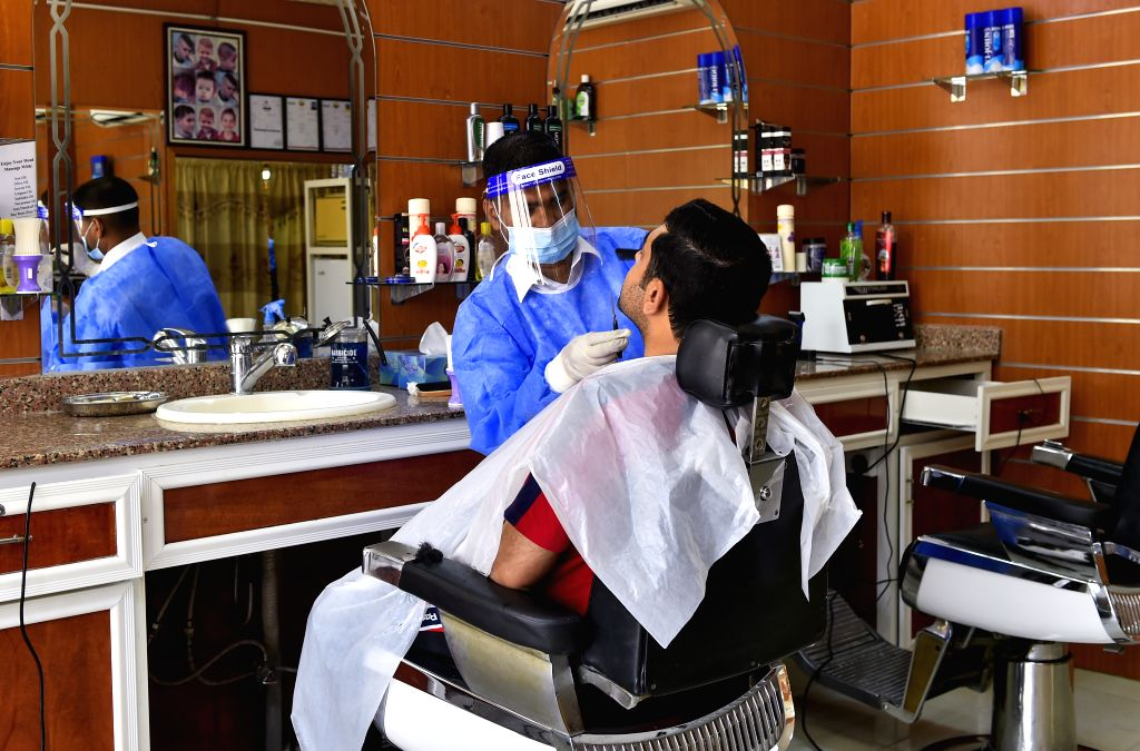 A barber wearing personal protective equipment serves a customer in Doha, capital of Qatar, July 30, 2020.