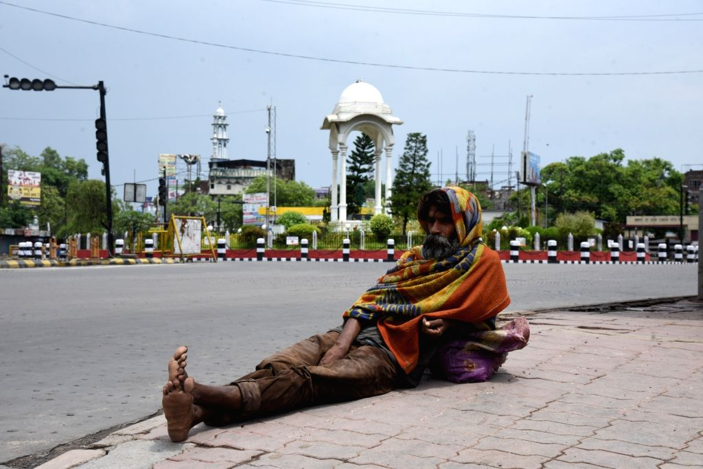 A beggar relaxes at the footpath along a deserted Patna street during the extended nationwide lockdown imposed to mitigate the spread of coronavirus; on Apr 26, 2020.