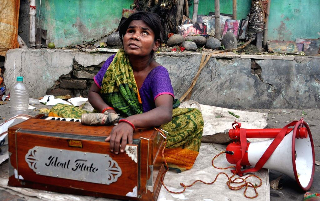 A beggar sings and plays harmonium in Kolkata on March 4, 2019.