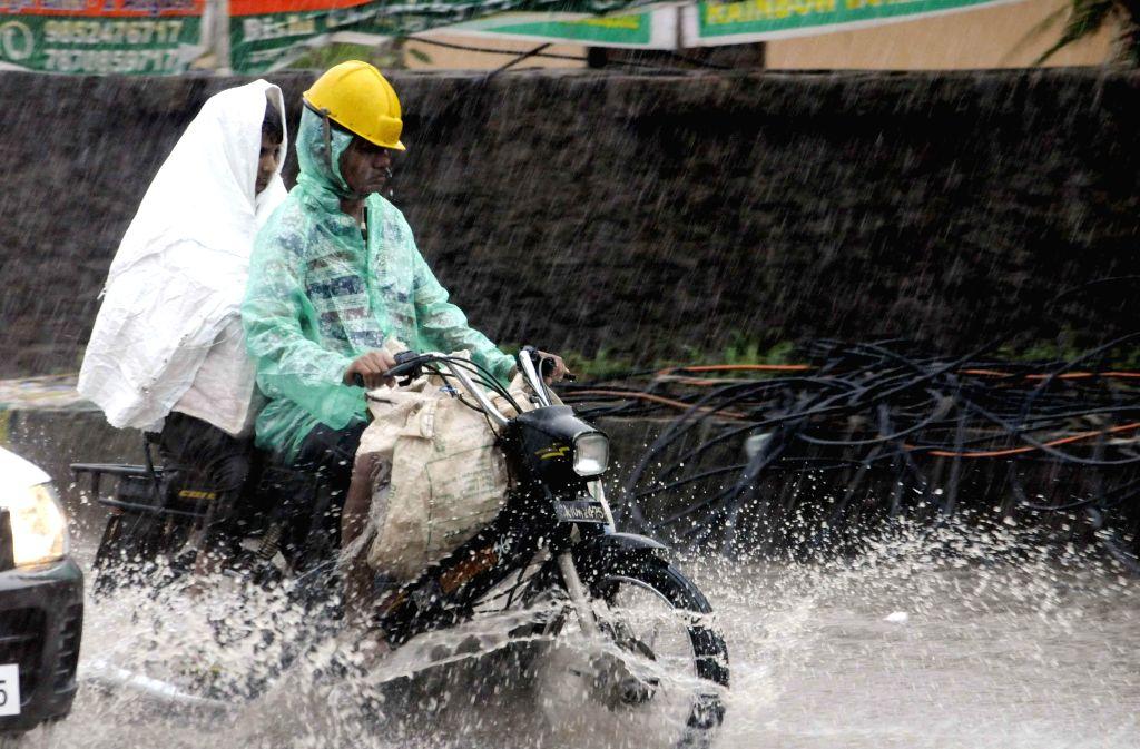 A biker struggles through waterlogged streets of Patna on Aug 14, 2014.
