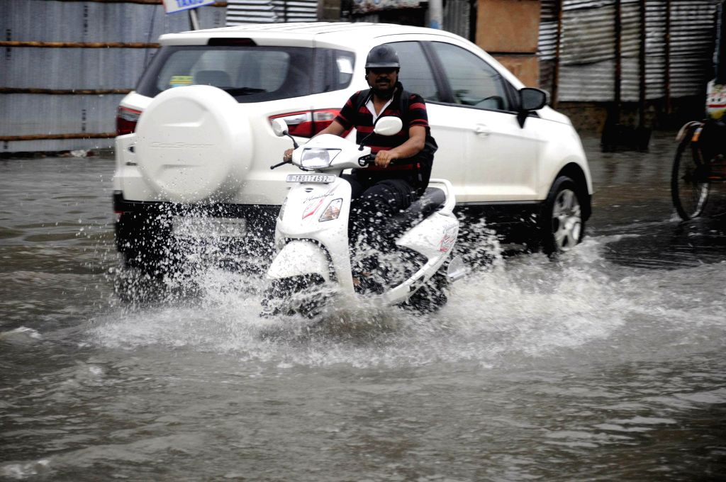 A biker wades through flooded roads during incessant rain in Agartala, the capital of northeastern state of Tripura on June 21, 2014. The Meteorological department has warned heavy rain with thunder .