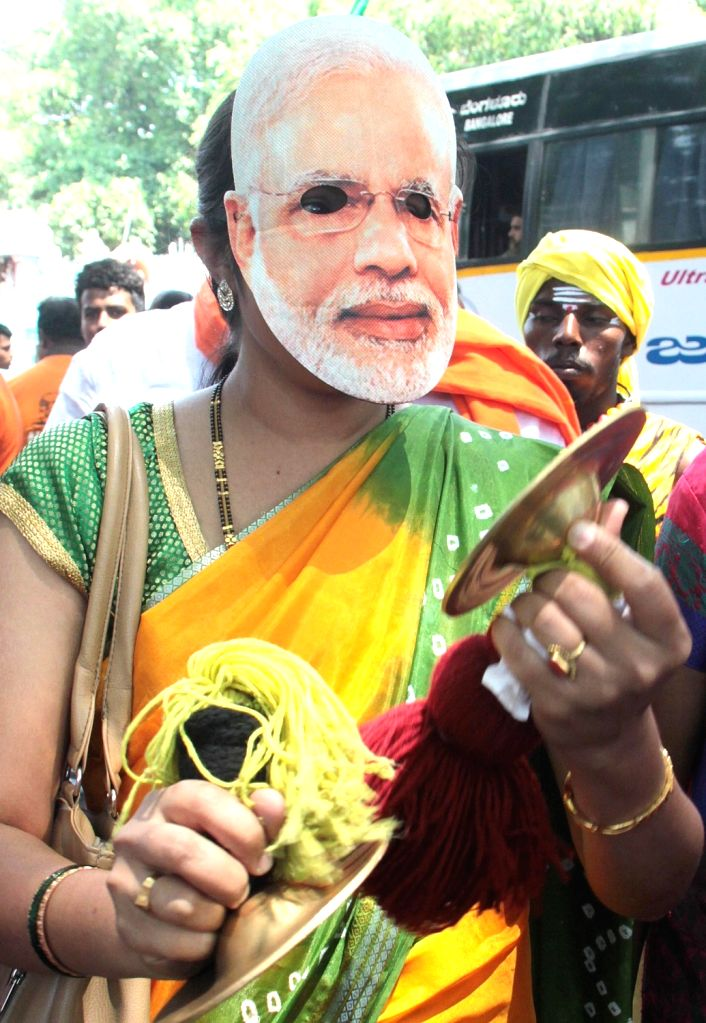 A BJP supporter wearing a mask of prime Minister Narendra Modi accompanies the party's Lok Sabha candidate from Bengaluru North, D.V. Sadananda Gowda as he heads to file his nomination for ... - Narendra Modi