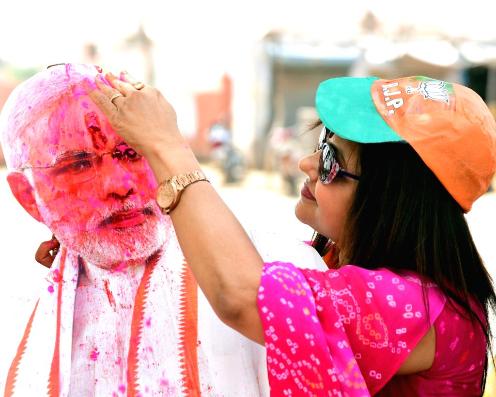 A BJP worker applies 'gulaal' to the cutout of Prime Minister Narendra Modi as she celebrates the party's performance after most exit polls showed the BJP-led NDA getting a comfortable ... - Narendra Modi