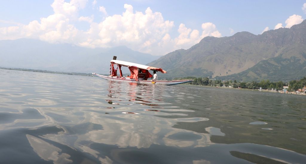 A boatman ferries a tourist on a Shikara across the waters of Dal Lake, in Srinagar on July 16, 2019.
