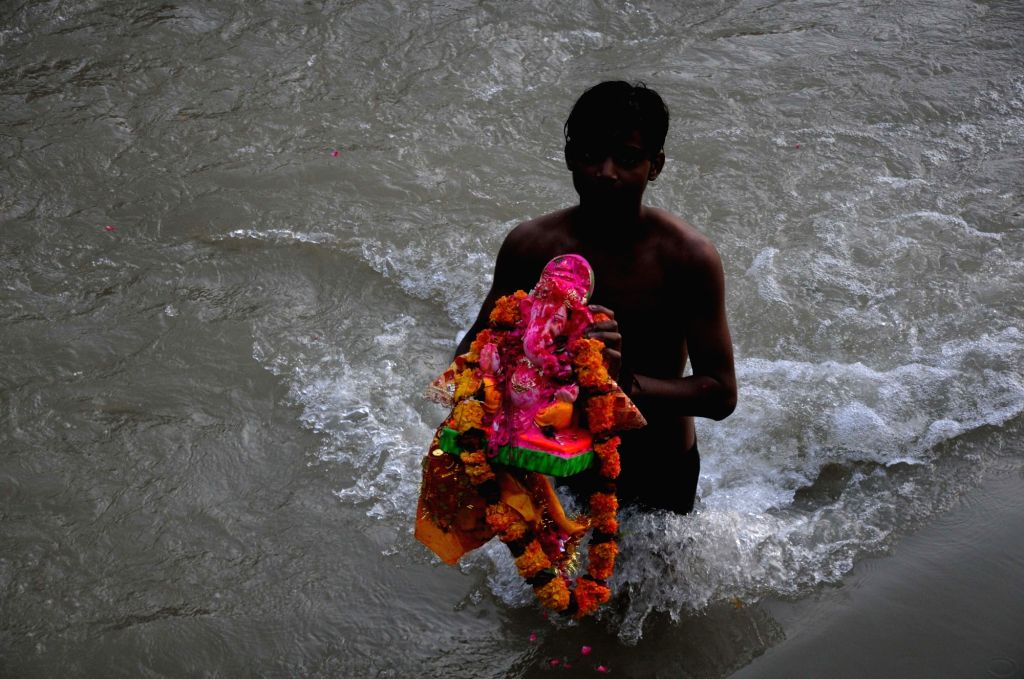 A boy carries an idol of Lord Ganesha to be immersed into a canal on the outskirts of Amritsar, on Sept 15, 2018.