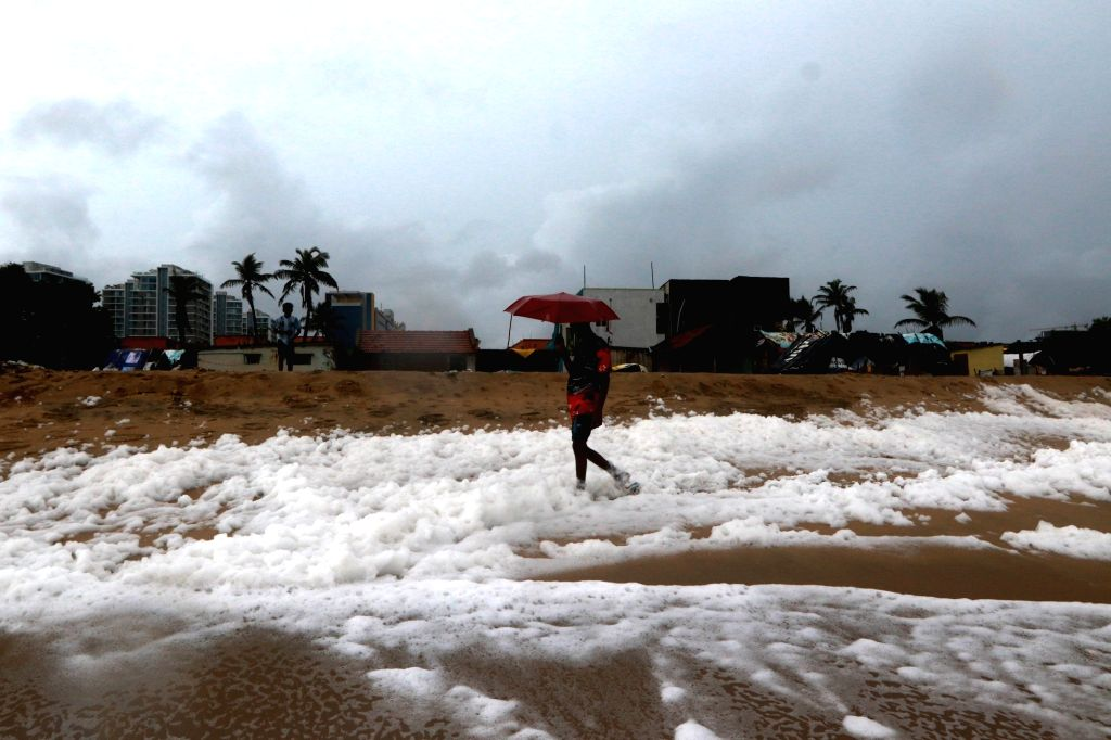A boy carrying an umbrella walks past the frothing sea shore of Marina Beach, in Chennai on Oct 30, 2019.