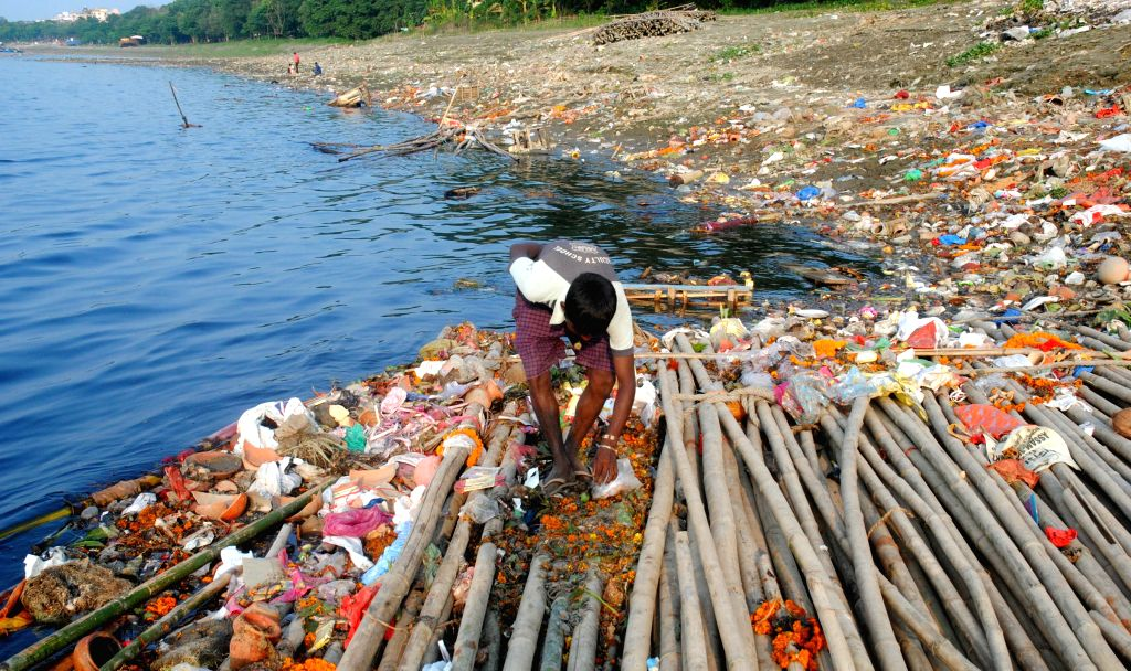 A boy collects garbage from the bank of river Brahmaputra after the immersion of Goddess Durga in Guwahati, on Oct 24, 2015.